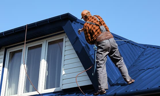 Roofer fixing a metal roof